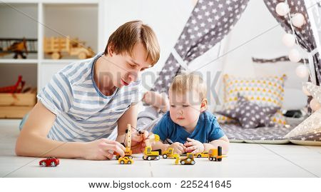 happy family father and son playing in toy car in playroom at home