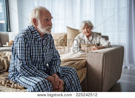 Upset Old Man Sitting On Bed With Sad Look. His Woman Sitting In Bed Under The Blanket And Looking A