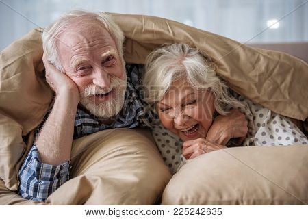 Cheerful Old Married Couple Lying In Bed Under Blanket. Woman Is Laughing And Man Is Looking At Came