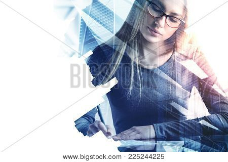 Attractive businesswoman doing paperwork on abstract city background. Finance and accounting concept. Double exposure