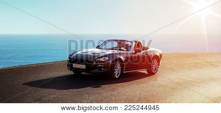 Young attractive couple posing in a convertible car, by the sea