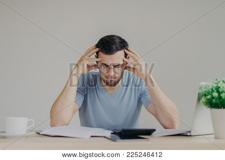 Brunet young male faces financial problems, not able to pay out mortagage, has desperate expression, makes calculations with calculator, isolated over grey background, uses modern technologies