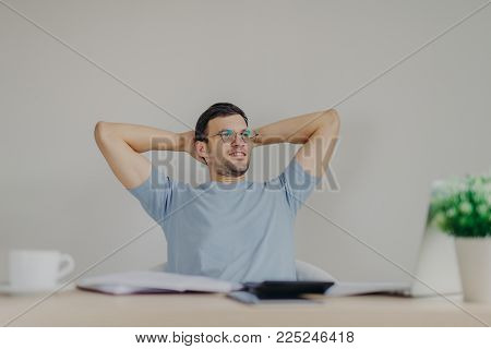Carefree male enterpreneur ready with financial report, being glad to realize that he recieves high net profit, sits at working desk with calculator, laptop computer, documentation. Accounting concept