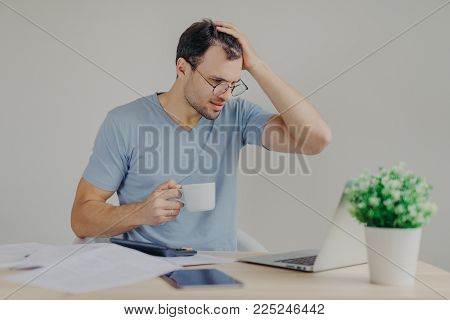 Desperate young male has financial crisis, scratches head in tension, tries to find solution, searches for loan, looks in puzzlement into laptop computer, drinks hot beverage, has many debts