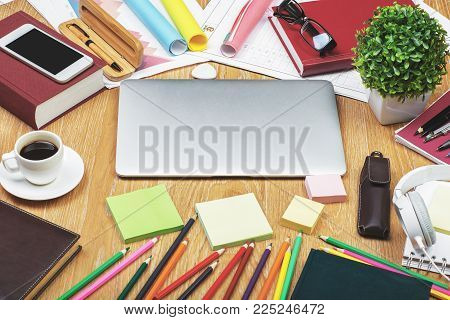 Close up of creative designer desktop with closed laptop and various colorful supplies. Mock up