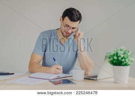 Serious brunet young male sits in front of opened laptop, talks on mobile phone and writes down notes, works through finances at workplace, isolated over grey background, has serious expression