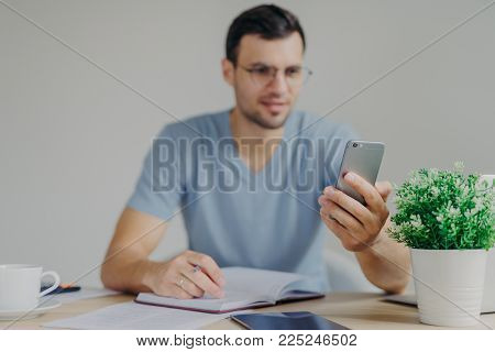 Modern smart phone in man`s hands. Busy male office worker recieves messages on mobile phone while makes some notes in diary, sits against cozy interior. Focus on cellular. Technology concept