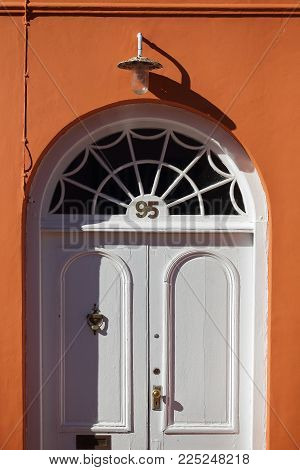 Old White Wooden Door In Orange Concrete Wall With The Light On Top , 95 Home Addresss Empty Abstrac