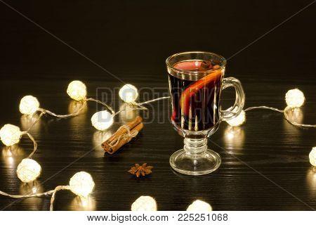 Mug Of Mulled Wine With Spices, Cinnamon Sticks, Star Anise. Illumination Of Rattan Lanterns. Black