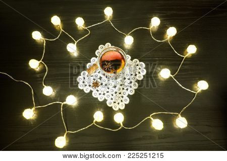 Mulled Wine With Spices On A Lacy Napkin And Cinnamon. Rattan Lanterns On Black Wooden Table