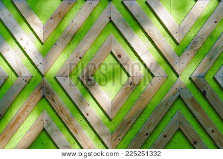 Panel made of green chipboard. Ornament of wooden slats, nailed to panel. Background with rhombuses made of wood. Texture with a diamond pattern.