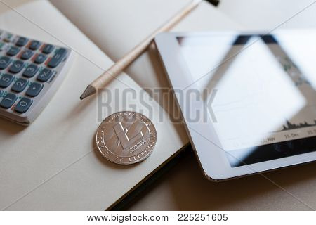 Close up view a litecoin silver, a stock graph on a tablet screen and blank note with calculator