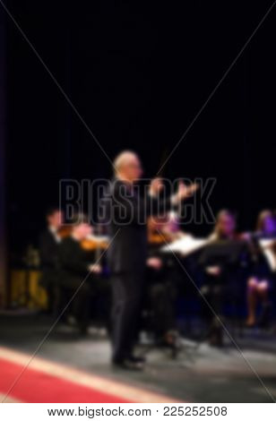Orchestra conductor  manages the orchestra.  musical concept. blurred background. Background for design, blur texture, actors on stage scene in concert. conducting .symphony
