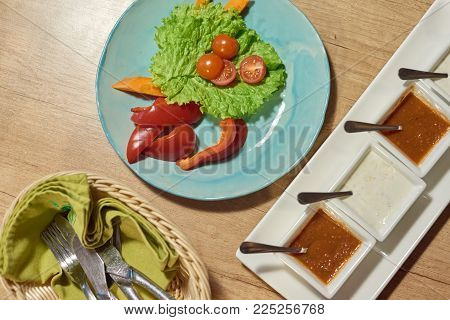 Top-view of vegetable salad, fried popatoes and different sauces, after meal