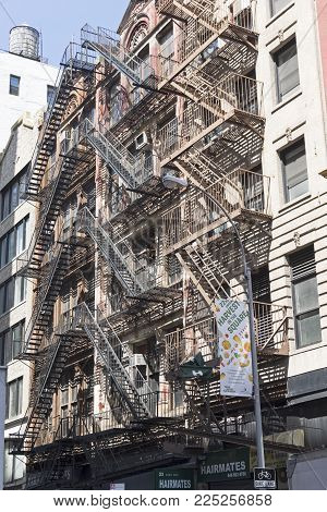 NEW YORK CITY - AUGUST 24, 2017: New York, Manhattan. Traditional for the old American cities fire escape staircases on the facade of the house. Beginning of Broadway.