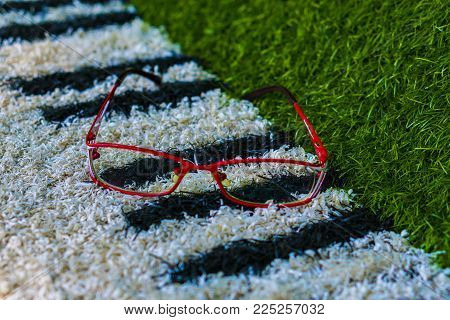 The glasses lie on the decorative surface. Eyeglasses lie in a red frame on the lawn or piano keys.