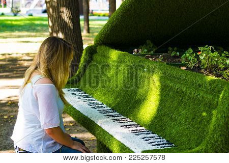 The girl is sitting at the piano. The tool is covered with a decorative cloth. The case is green. Keyboard of natural colors. A woman in glasses plays the decorative piano.