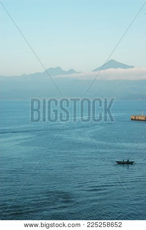 A small boat with two fishermen is dwarfed by the vastness of a blue bay. Mountains rise in the distance. A bank of low-lying clouds cover the base of the mountain, but the sky is clear and blue. The end of a stone pier can just be seen. The water is stil