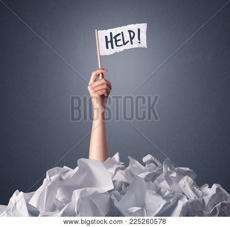 Female hand emerging from crumpled paper pile holding a white flag with help written on it