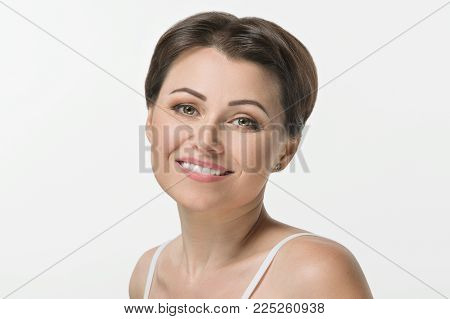Close-up shot of a beautiful mid adult woman smiling on white background.