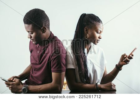 African Couple Holding Mobile Phones In Hand