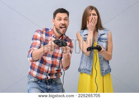 Emotional couple with video game controllers on grey background