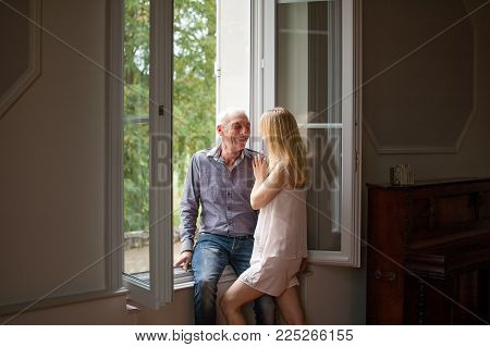 Senior Man in Jeans and Shirt Hugging His Young Blond Wife Standing near the Window in Their Home During Summer Time