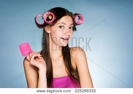 cute smiling girl doing a beautiful hairstyle with curlers
