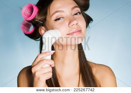 a cute young girl cleanses the skin of the face with an electric brush, on the head of curlers