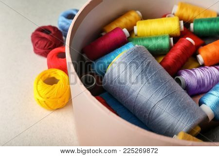 Box with color sewing threads and crocheting clews on table, closeup