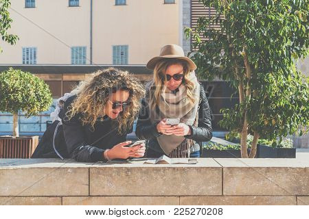 Two young women tourists in sunglasses with backpacks stand on city street and are looking for way on map and navigation system in smartphone. Girls use digital gadgets. Sunny day. Vacation.