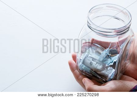 Man Holds A Glass Jar For Donations With Place For Text On A White Background
