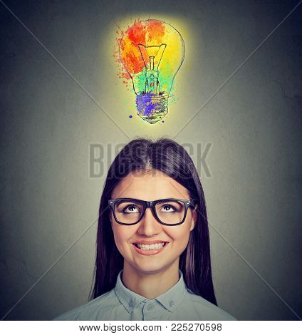 Portrait Of A Woman With Glasses And Creative Idea Looking Up At Colorful Light Bulb On Gray Backgro