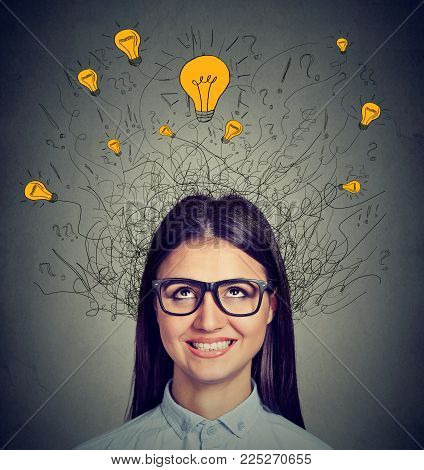 Young Woman With Many Ideas Light Bulbs Above Head Looking Up Isolated On Gray Wall Background. Eure