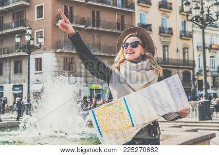 Young female tourist is standing on street of European city near fountain, holding map and pointing at something with her finger. Girl is looking for way on map, looks at sights. Tourism, vacation.
