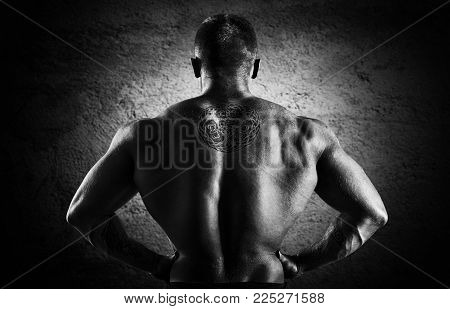 Huge Weightlifter Stands With His Back To The Camera And Shows His Huge Back.