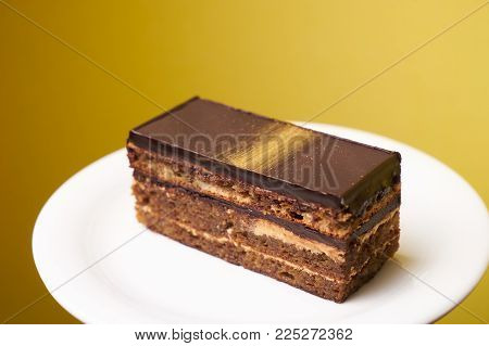 Opera cake slice on a white plate on cake board. Delicious French dessert cake opera on yellow background, close-up