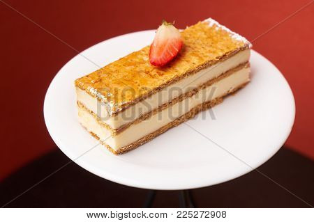 Milfey napoleon cake with fresh strawberries. Piece of layered cake with pastry cream custard on white plate on cake board, close-up. Delicious homemade dessert.