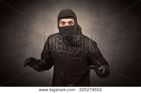 Burglar standing in black clothes and balaclava on his head.