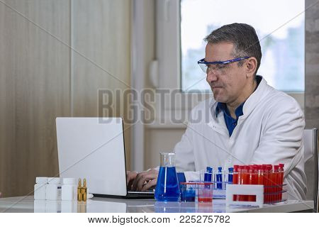 Scientist Typing On Laptop Computer In Biochemistry Lab. Lab Worker Typing Test Report On Laptop Com