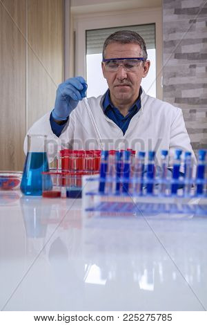 Researcher Working with a Pipette in a Biochemistry Lab. Glass laboratory chemical test tubes with red and blue liquid.Man wears protective goggles and blue gloves. poster