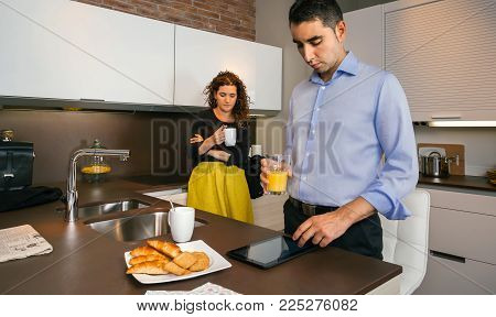 Young man looking electronic tablet while curly woman having fast coffee in home before go to work
