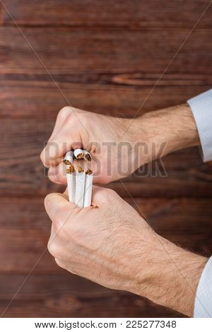 Man breaks cigarettes in his hands. Quit smoking. Concept.