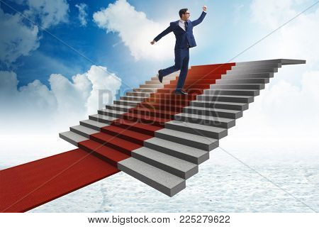 Young businessman climbing stairs and red carpet into sky