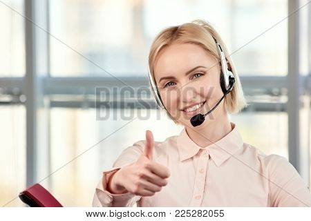 Female blond mature call center operator showing thumbs up. Smiling call center agent giving thumb up against windows background.