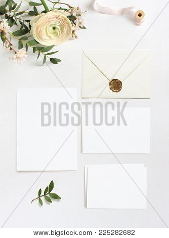 Feminine wedding, birthday desktop mock-ups. Blank greeting cards, envelope. Eucalyptus branches, pink cherry tree blossoms and Persian buttercup flowers, white table background. Flat lay, top view.