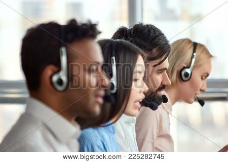 Bearded caucasian man working in call center amoung colleagues. Young bearded male employee working with a headset and accompanied by his team.