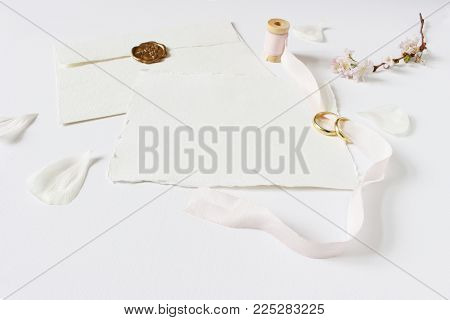 Wedding greeting card, invitation with two golden rings, cherry tree blossoms, white rose petals, spool of pink silk ribbon and handmade envelope with a seal, feminine styled stock image.