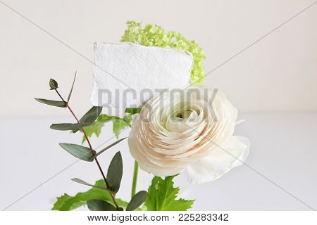 Wedding or birthday mock-up scene with floral bouquet of Persian buttercup, Ranunculus flower and eucalyptus leaves with blank paper greeting card, feminine styled stock image.