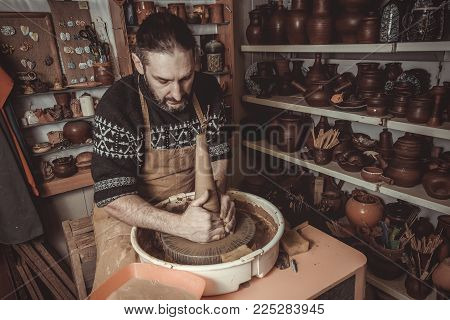 Adult male potter master mashing the clay.
